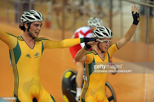 Australia's Micheal Freiberg and Cameron Meyer celebrate after winning medals in the men's scratch cycling at the Indira Gandhi Sports Complex during...