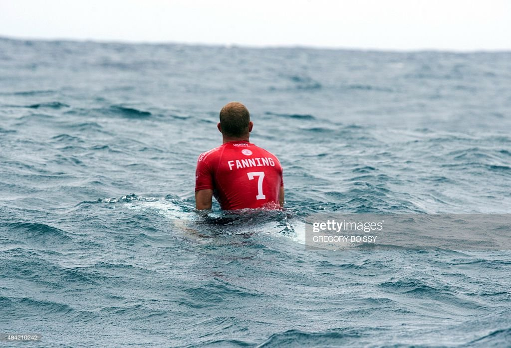 Australia's Mick Fanning sits on his board in the sea during the kick off of the 2015 Billabong Pro Tahiti World Surf league tour no7 along the...