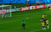 Australia's midfielder and captain Mile Jedinak scores on a penalty kick during a Group B football match between Australia and the Netherlands at the...