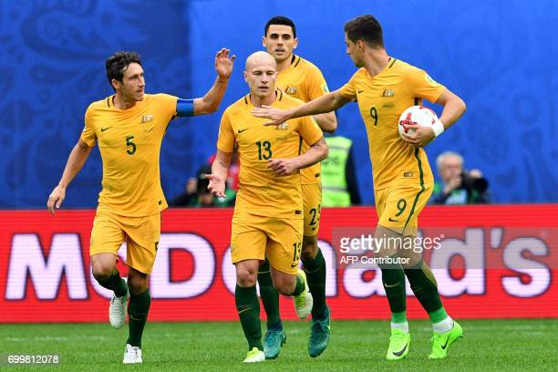 Australia's midfielder Mark Milligan is congratulated by midfielder Aaron Mooy and forward Tomi Juric afetr scoring in a penalty during the 2017...