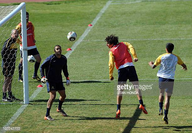 Australia's midfielder Mile Jedinak heads the ball past goalkeeper Adam Federici during a training session at Ruimsig Stadium in Roodepoort on June...