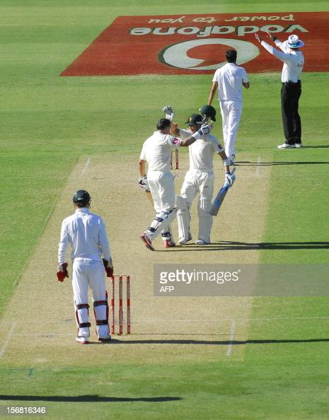 Australia's Mike Hussey celebrates his 100 runs against South Africa with teammate Michael Clarke on the first day of the second cricket Test match...