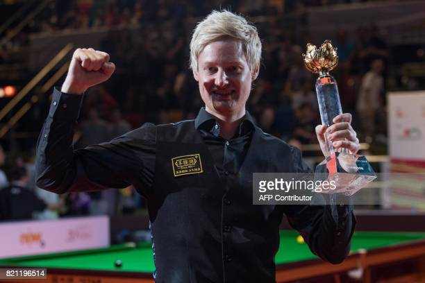 Australia's Neil Robertson celebrates with the trophy after victory against Britain's Ronnie O'Sullivan during the final of the Hong Kong Masters...