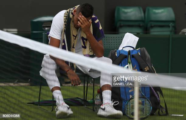 Australia's Nick Kyrgios reacts at the end of the second set before retiring from his men's singles first round match against France's PierreHugues...