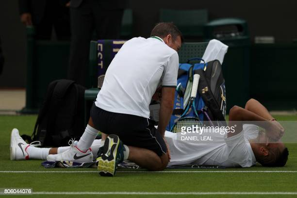 Australia's Nick Kyrgios receives medical treatment at the end of the second set before retiring from his men's singles first round match against...