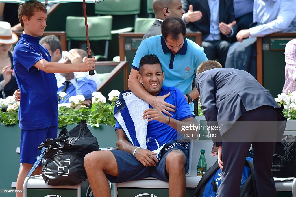 Australia's Nick Kyrgios (C) receives treatment for his shoulder during his men's third round match against France's Richard Gasquet at the Roland Garros 2016 French Tennis Open in Paris on May 27, 2016. / AFP / Eric FEFERBERG