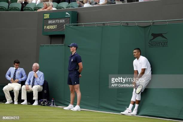 Australia's Nick Kyrgios rests against the back of the court during a break in play against France's PierreHugues Herbert during their men's singles...