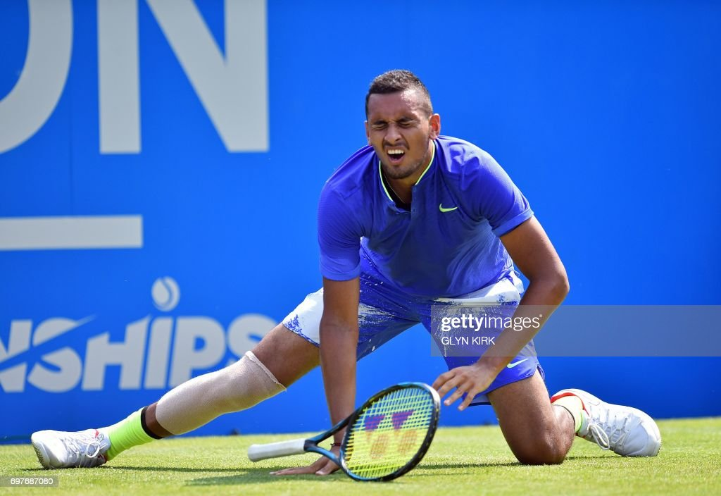 TOPSHOT - Australia's Nick Kyrgios slips during his men's singles 1st round match against Donald Young of the US at the ATP Aegon Championships tennis tournament at Queen's Club in west London on June 19, 2017. Nick Kyrgios suffered a fresh injury blow ahead of Wimbledon as the Australian star was forced to retire from his Queen's Club first round clash with Donald Young on Monday. /