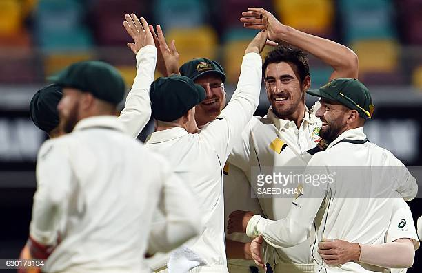 Australia's paceman Mitchell Starc celebrates his wicket of Pakistan's batsman Sarfraz Ahmed with teammates during the fourth day of the daynight...
