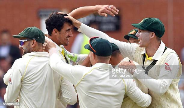 TOPSHOT Australia's paceman Mitchell Starc celebrates with teammates after dismissing England's batsman Mark Stoneman on the fourth day of the second...