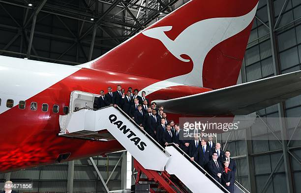 Australia's players and officials pose for a group photograph on the stairs of a Qantas airlines plane during the announcement of the Australian...