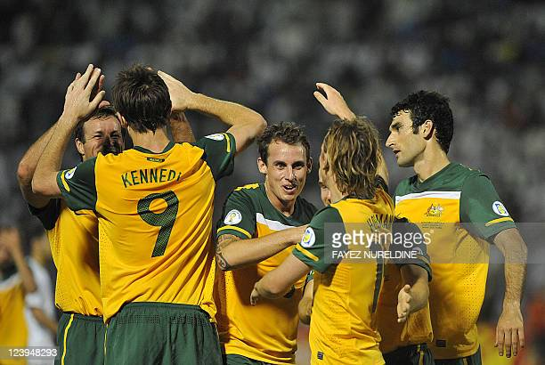 Australia's players celebrate their second goal scored against Saudi Arabia during their 2014 World Cup Asian zone qualifying football match in...