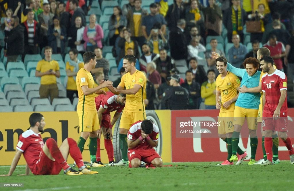 Australia's players celebrate their victoy as Syrian players look dejected after their 2018 World Cup football qualifying match in Sydney on October 10, 2017. /