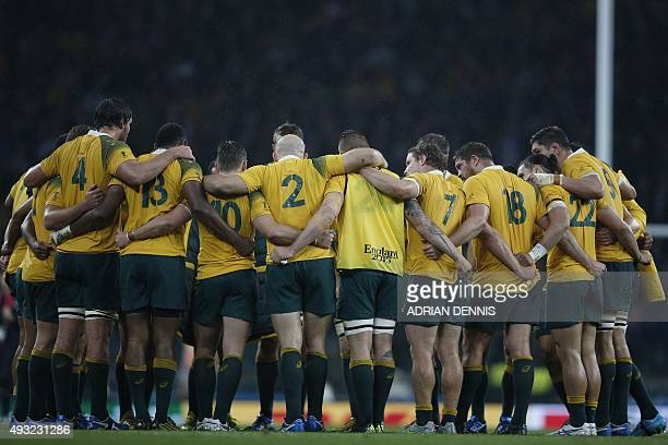 Australia's players huddle as they celebrate after winning a quarter final match of the 2015 Rugby World Cup between Australia and Scotland at...