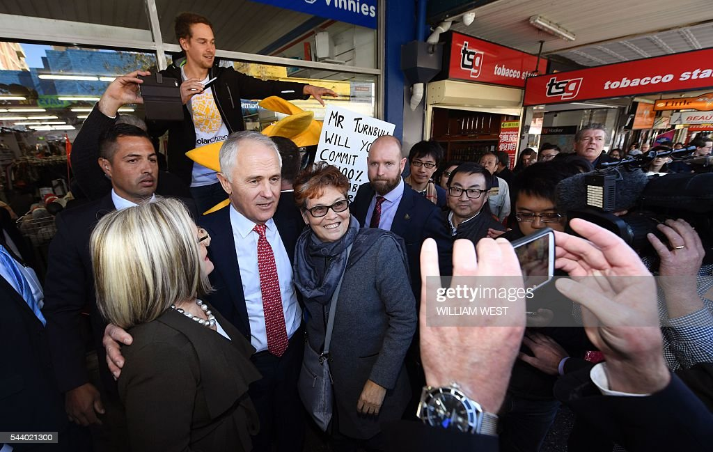 Australia's Prime Minister Malcolm Turnbull (L) and wife Lucy (C) have a selfie taken with locals during a street walk in Sydney on July 1, 2016, as Australia's leaders make last-gasp pitches to wow voters with polls on the eve of elections pointing to a cliffhanger. Liberal Turnbull and Labor opposition leader Bill Shorten both opted to campaign in Sydney on their final day on the hustings as a poll in The Sydney Morning Herald showed them locked in a dead heat on a two-party basis. / AFP / WILLIAM