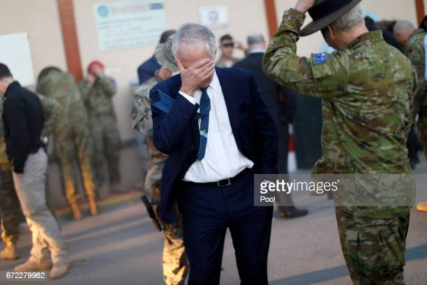 Australia's Prime Minister Malcolm Turnbull shields his eyes from dust kickedup from a helicopter passing overhead at Resolute Support headquarters...