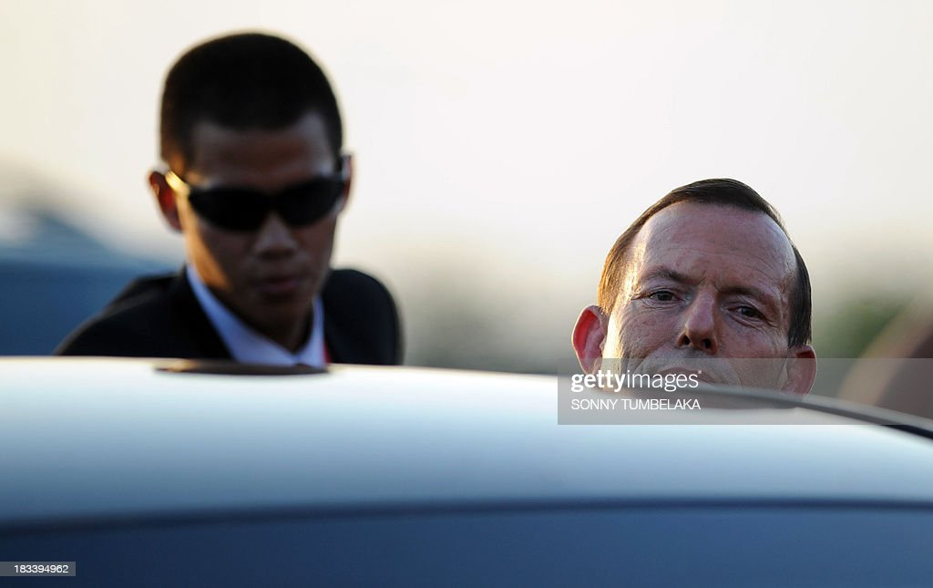 Australia's Prime Minister Tony Abbott (R) gets into a car upon his arrival at Ngurah Rai International Airport in Denpasar on the Indonesian resort island of Bali to take part in the Asia-Pacific Economic Cooperation (APEC) summit on October 6, 2013. Leaders of the 21-member APEC grouping are arriving in Bali ahead of the leader's summit on October 7-8 in nearby Nusa Dua.