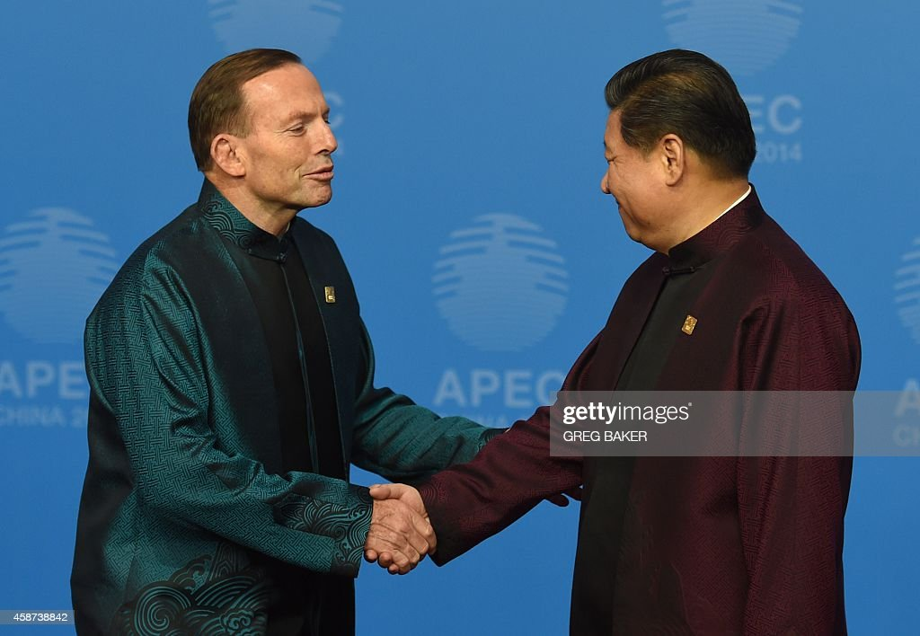 Australia's Prime Minister Tony Abbott (L) is welcomed by Chinese President Xi Jinping as he arrives for Asia-Pacific Economic Cooperation (APEC) Summit banquet at the National Aquatics Center in the Chinese capital on November 10, 2014. Top leaders and ministers of the 21-member APEC grouping are meeting in Beijing from November 7 to 11. AFP PHOTO/Greg BAKER