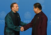 Australia's Prime Minister Tony Abbott is welcomed by Chinese President Xi Jinping as he arrives for AsiaPacific Economic Cooperation Summit banquet...