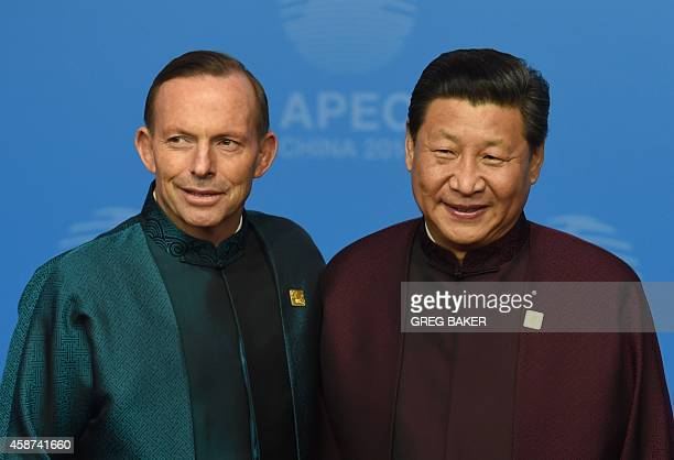 Australia's Prime Minister Tony Abbott poses with Chinese President Xi Jinping upon arrival for AsiaPacific Economic Cooperation Summit banquet at...