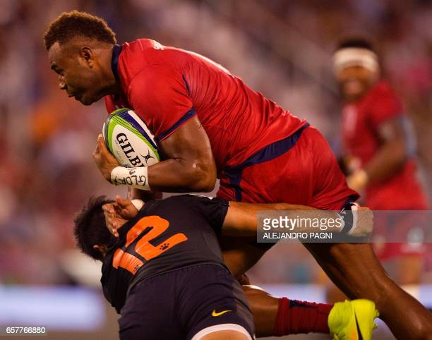 Australia's Queensland Reds flyhalf Eto Nabuli is tackled by Argentina's Jaguares centre Jeronimo De la Fuente during their Super Rugby match at Jose...