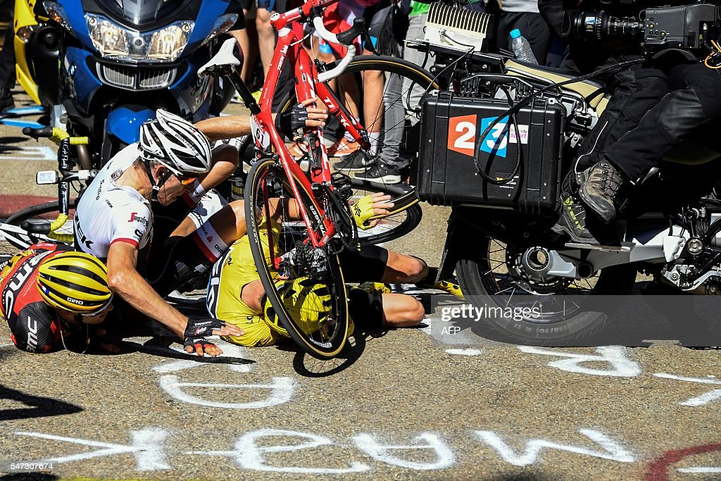 TOPSHOT - (From L) Australia's Richie Porte, Netherlands' Bauke Mollema and Britain's Christopher Froome, wearing the overall leader's yellow jersey, fall on the ground during the 178 km twelvelth stage of the 103rd edition of the Tour de France cycling race on July 14, 2016 between Montpellier and Chalet-Reynard. PAPON