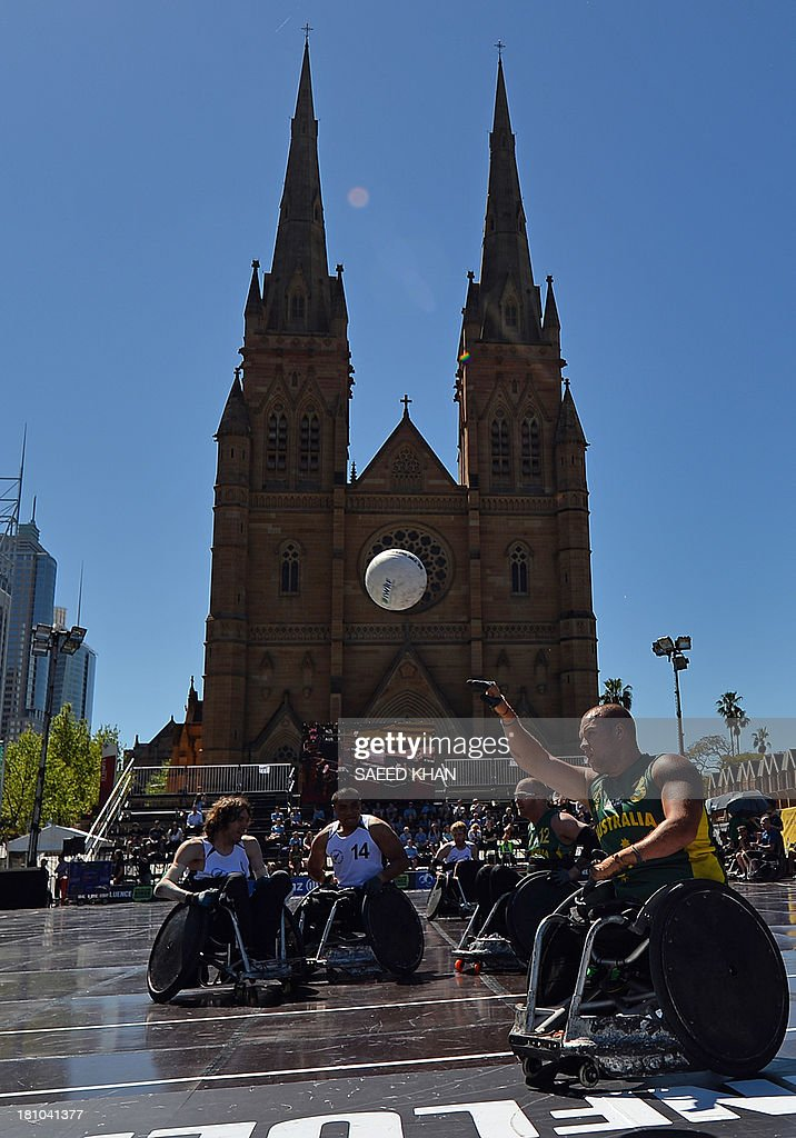 Australia's Ryley Batt (R) scores a goal against New Zealand during their Wheelchair Rugby Tri-Nations match in front of St. Mary's Cathedral in Sydney on September 19, 2013. Wheelchair Rugby, which is also know as mederball due to its aggressive, full-contact nature, originated in Canada in 1977 and combines the elements of basketball, football and ice hockey. AFP PHOTO / Saeed KHAN USE