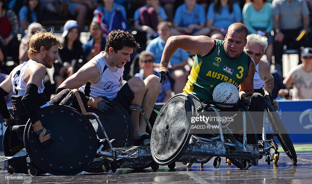Australia's Ryley Batt (R) tries to avoid a tackle during their Wheelchair Rugby Tri-Nations match against New Zealand in front of St. Mary's Cathedral in Sydney on September 19, 2013. Wheelchair Rugby, which is also know as mederball due to its aggressive, full-contact nature, originated in Canada in 1977 and combines the elements of basketball, football and ice hockey. AFP PHOTO / Saeed KHAN USE