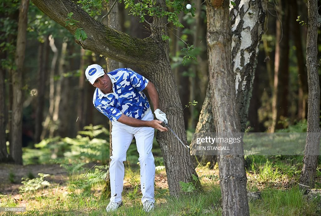 Australia's Scott Hend plays his second shot out of the trees on the 13th hole during the third day of the PGA Championship at Wentworth Golf Club in Surrey, south west of London, on May 28, 2016. / AFP / BEN