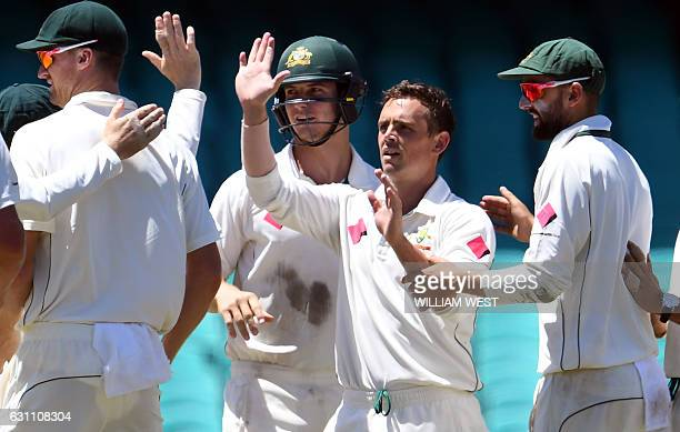 Australia's spinner Steve O'Keefe is congratulated by teammates after dismissing Pakistan batsman Yasir Shah on the final day of the third cricket...