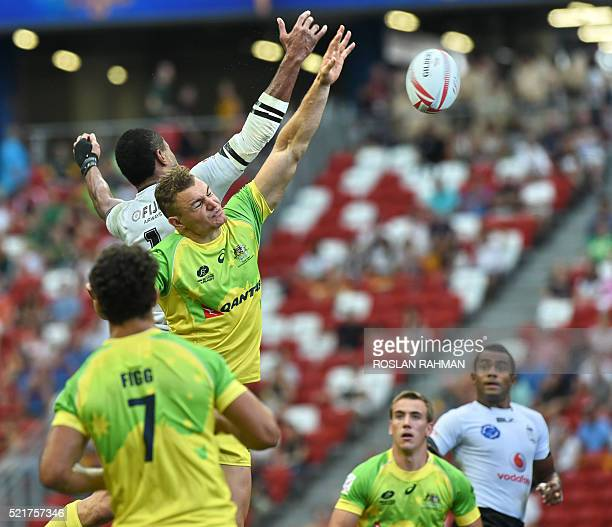 Australia's Stephan Van der Walt and Fiji's Apisai Domolailai reach for the ball during their cup quarterfinal match at the Singapore Sevens rugby...