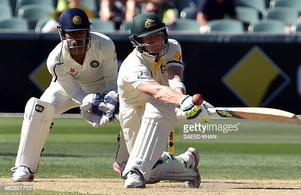 Australia's Steve Smith tries to play a reverse sweep as India's wicketkeeper Wriddhiman Saha looks on during the fourth day of the first test...