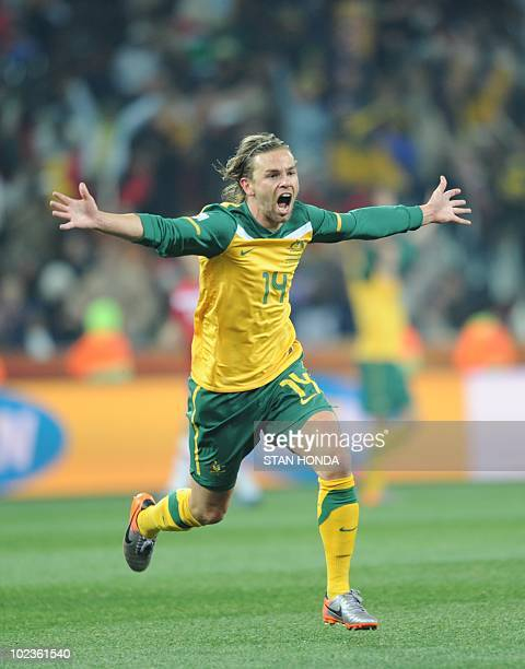 Australia's striker Brett Holman celebrates with teammates after scoring during the Group D first round 2010 World Cup football match Australia vs...