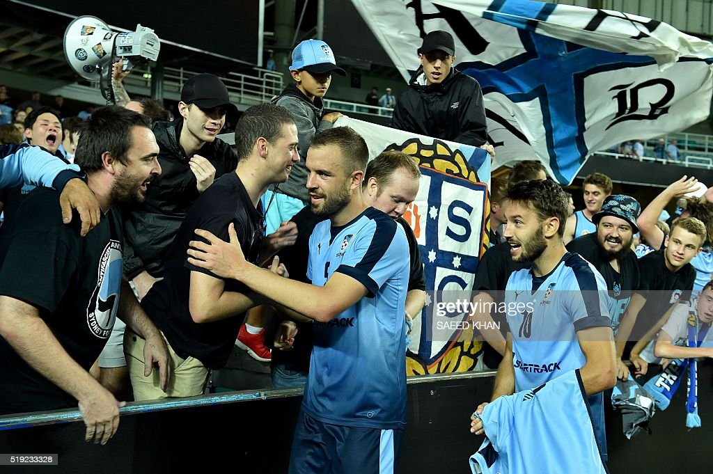 Australia's Sydney FC players Matt Jurman(L)and Milos Ninkovic celebrate with fans after victory against South Korea's Pohang Steelers after their Asian Champions League football match in Sydney on April 5, 2016. / AFP / SAEED