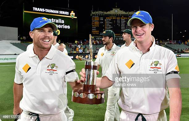 Australia's team captain Steve Smith and teammate David Warner smile as they walk back with the TransTasman trophy after defeating New Zealand in the...