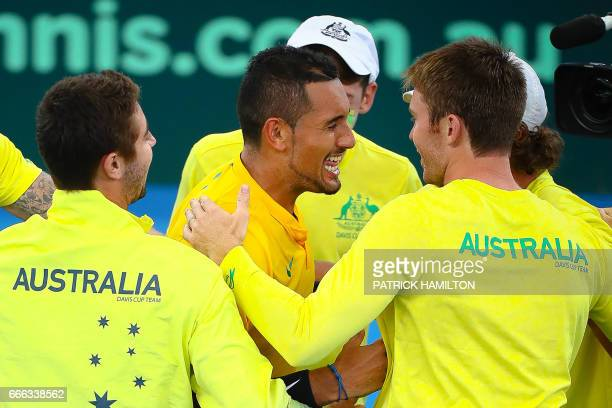 Australia's team members hug Nick Kyrgios as they celebrate Australia's victory over the US after Kyrgios' match against Sam Querrey in the world...