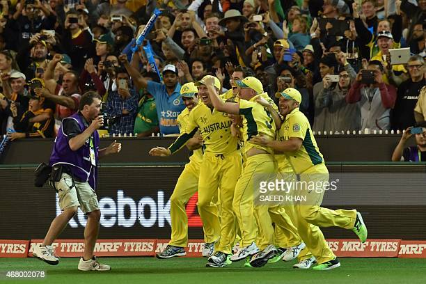 Australia's teammates celebrate victory against New Zealand during the 2015 Cricket World Cup final between Australia and New Zealand in Melbourne on...