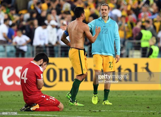 TOPSHOT Australia's Tim Cahill celebrates with teammate Jackson Irvine as Syria's Tamer Hag Moihamad reacts after Australia defeated Syria in their...