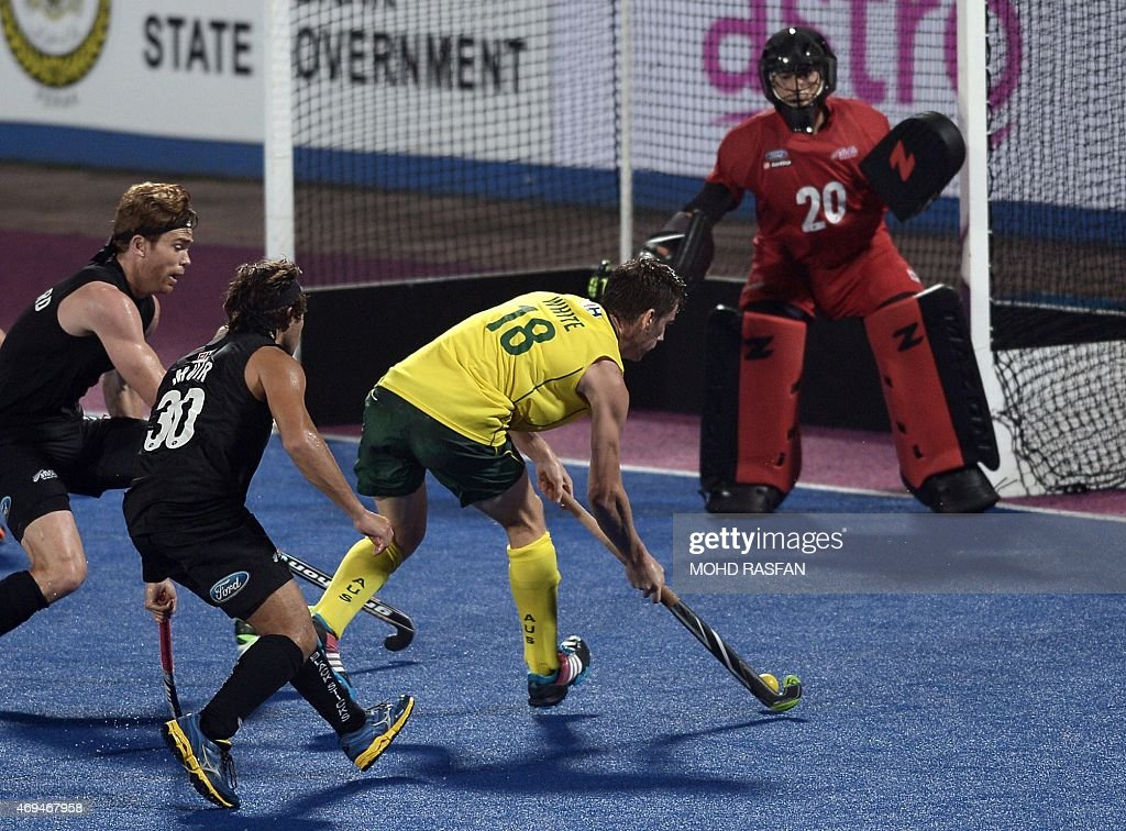 Australia's Tristan White vies for the ball against New Zealand players during the Sultan Azlan Shah Cup men's field hockey tournament finals in...