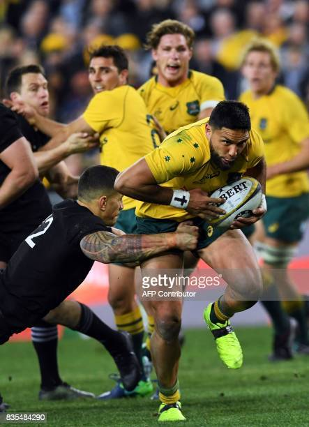 Australia's wing Curtis Rona avoids a tackle by New Zealand's centre Sonny Bill Williams during the Rugby Championship test match between Australia...