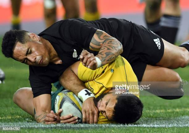 Australia's wing Curtis Rona scores a try as he is tackled by New Zealand's scrumhalf Aaron Smith during the Rugby Championship test match between...