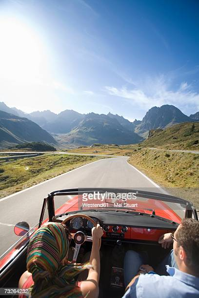 Austria, Alps, Couple driving in convertible car, rear view