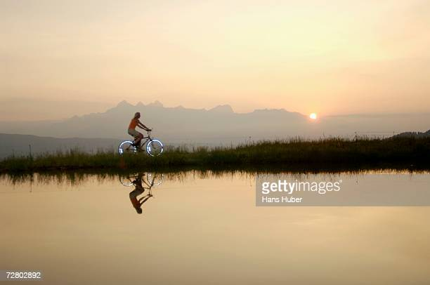Austria, Alps, Woman riding bicycle by lake, side view