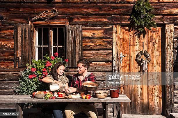 Austria, Altenmarkt-Zauchensee, couple having a break at alpine cabin