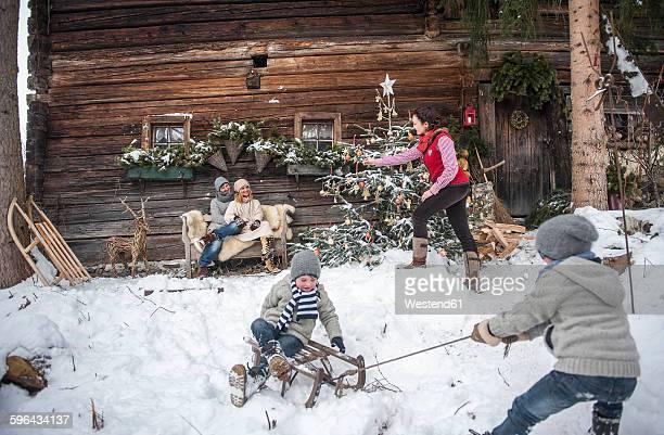 Austria, Altenmarkt-Zauchensee, family in front of farmhouse at Christmas time