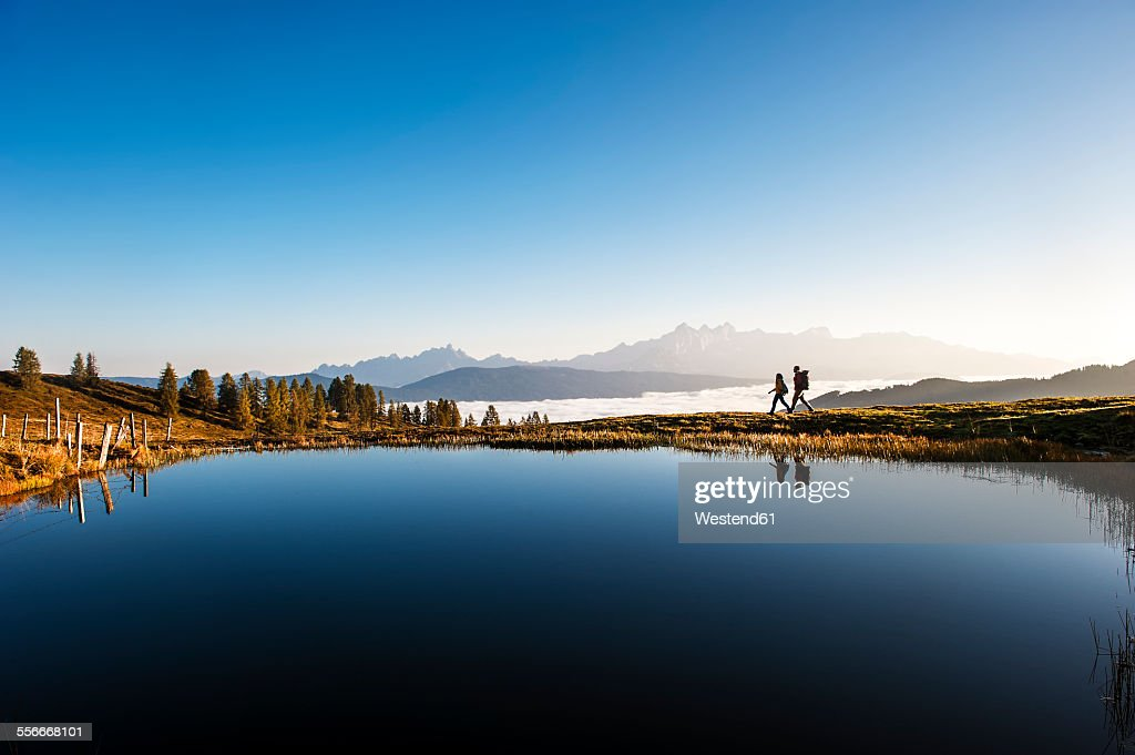 Austria, Altenmarkt-Zauchensee, hikers at mountain lake in the Lower Tauern : Photo