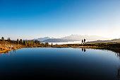 Austria, Altenmarkt-Zauchensee, hikers at mountain lake in the Lower Tauern