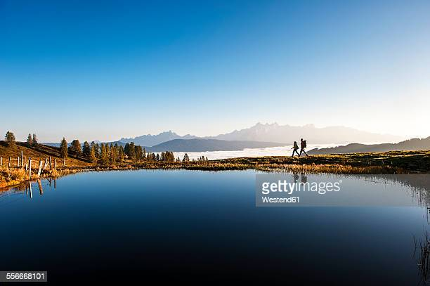 Austria, Altenmarkt-Zauchensee, hikers at mountain lake in the Lower Tauern