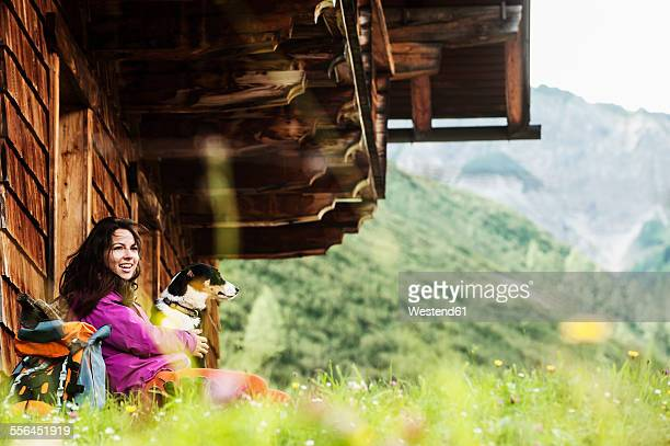 Austria, Altenmarkt-Zauchensee, young woman and dog in front of an Alpin cabin