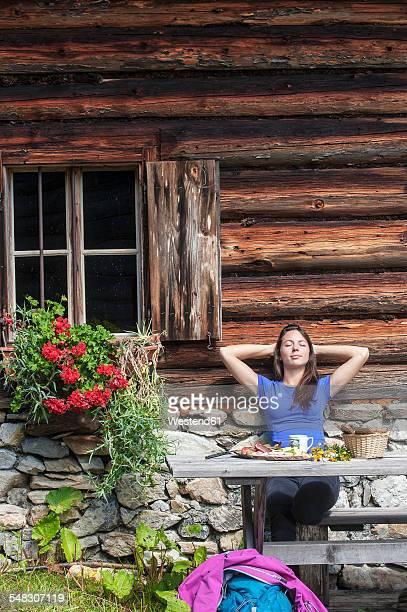 Austria, Altenmarkt-Zauchensee, young woman realxing at alpine cabin